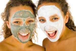 Happy young women with masks anti-aging. They're on white background. Front view