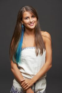 Portrait of happy smiling funky young female with blue hair lock, over dark background