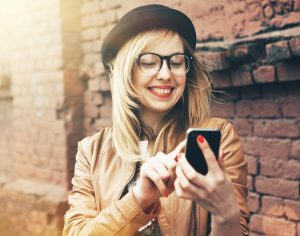 City lifestyle stylish hipster girl using a phone texting on smartphone app in a street